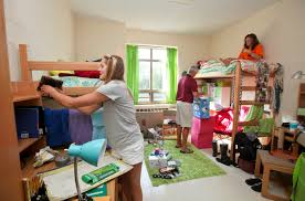 Roommates arrange and assemble their new dorm room.