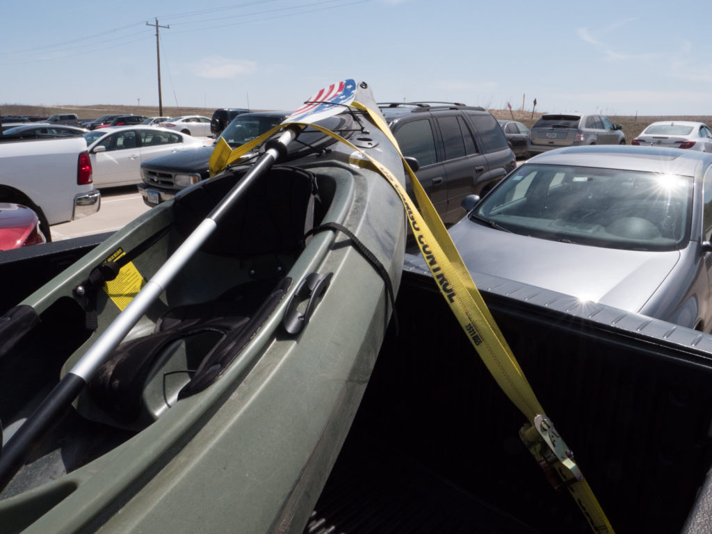 yellow ratchet straps in truck bed holding a kayak secure