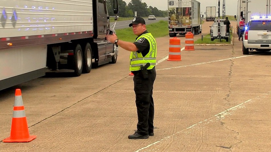 CVSA inspection officer directing traffic to side of road