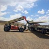 large forklift loading cargo onto flatbed truck