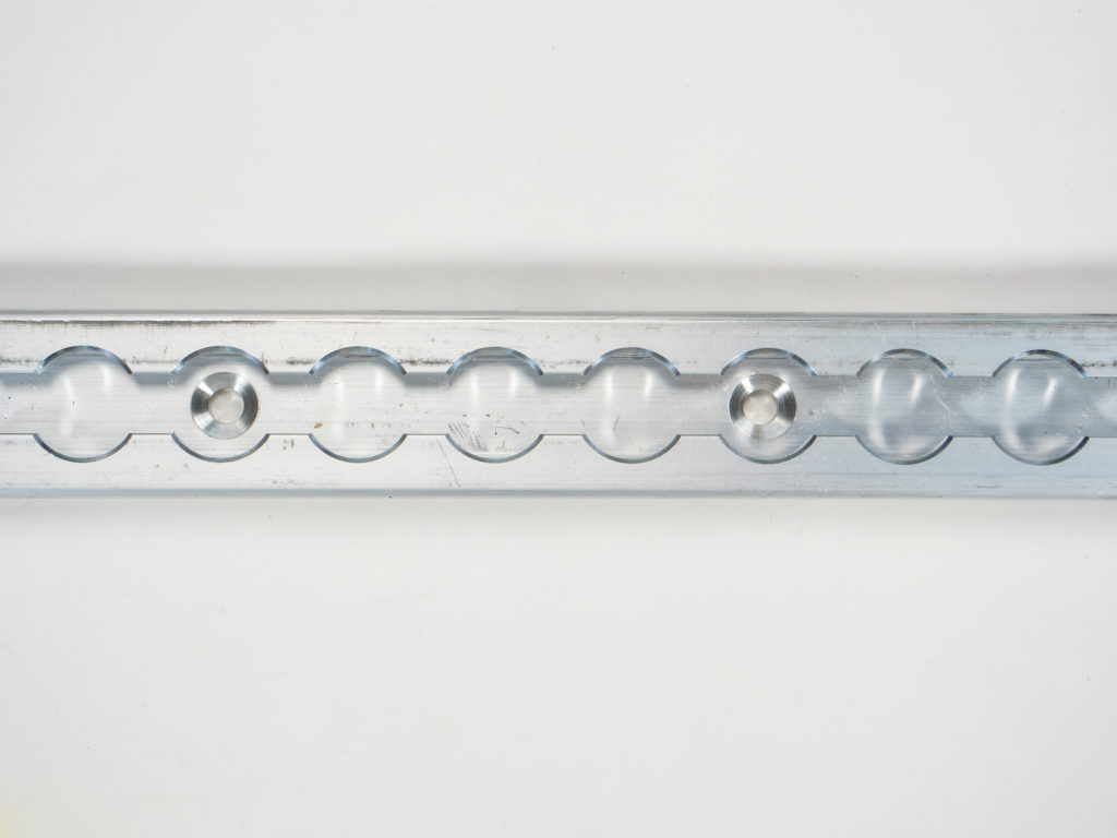 up-close shot of an L Track rail with pre drilled holes